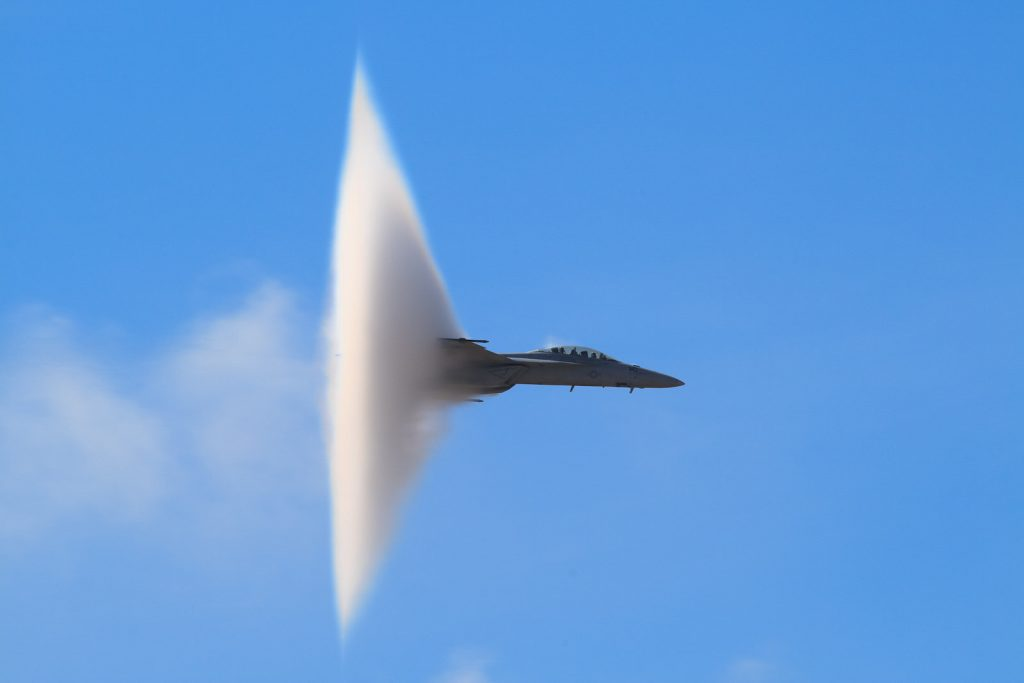 Vapor cone engulfs jet as it passes through the speed of sound.